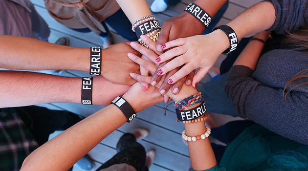 People's hands all in the middle with the Zeno fearless bracelets on