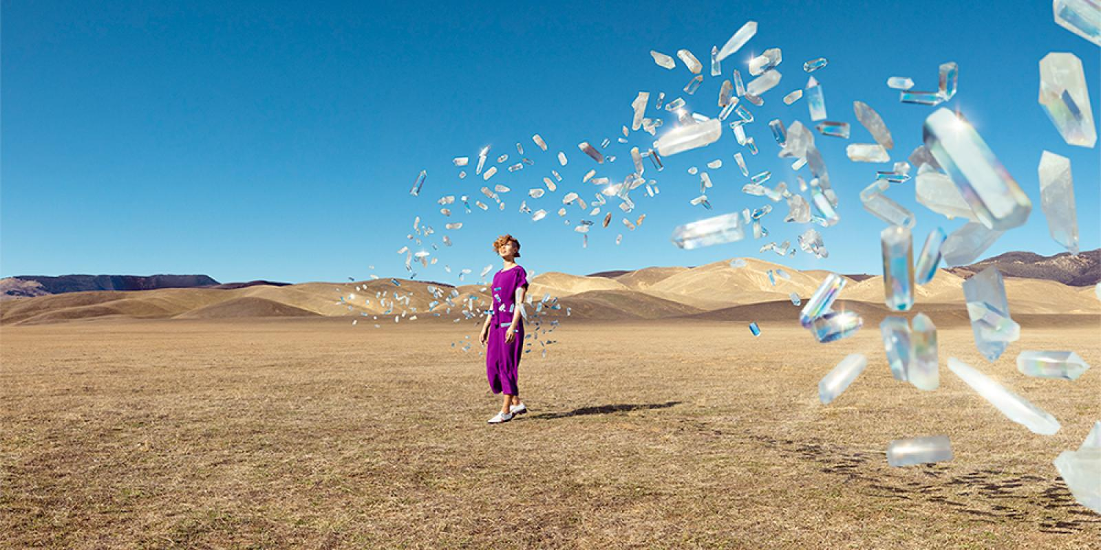 Image of a woman on a desert with crystals flying at her