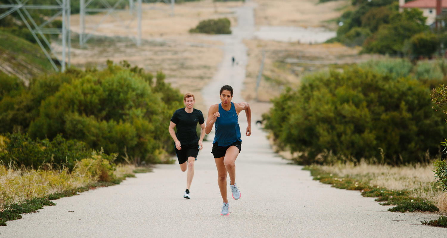 A man and a woman running up a hill with Asics shoes on