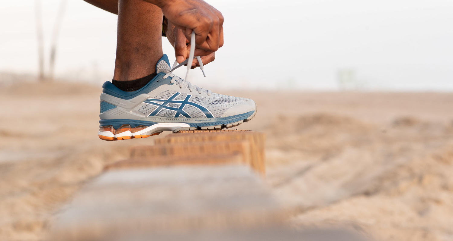 Zoomed up image of an Asics sneaker on a rockin a sandy location