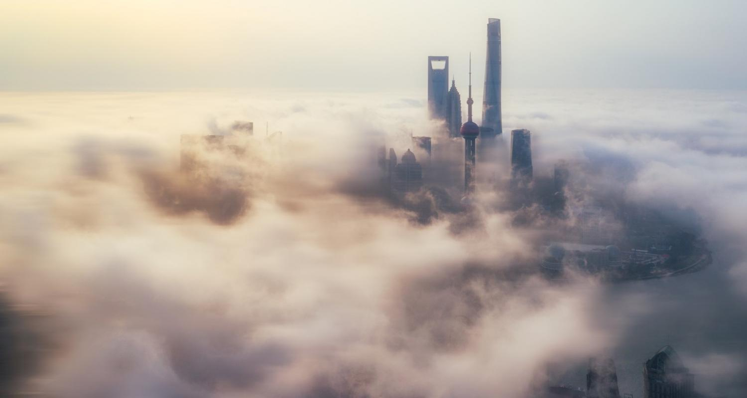 Image of pink and white clouds over a foggy utopian city