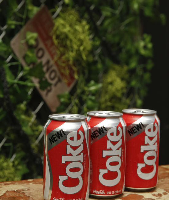3 Coca-Cola Bottles On a Bench