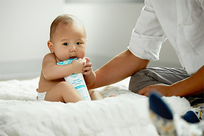 Baby eating a lotion bottle on a white comforter
