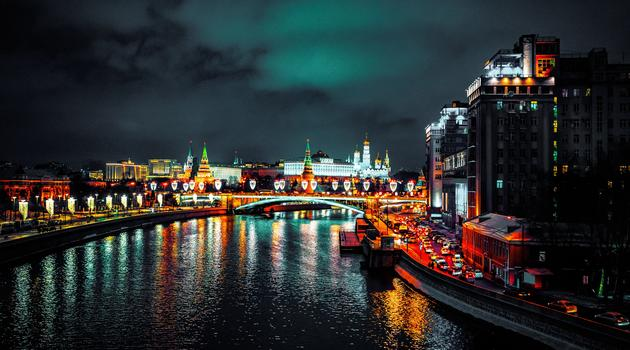 Building beside body of waters with colored lights reflecting in Russia