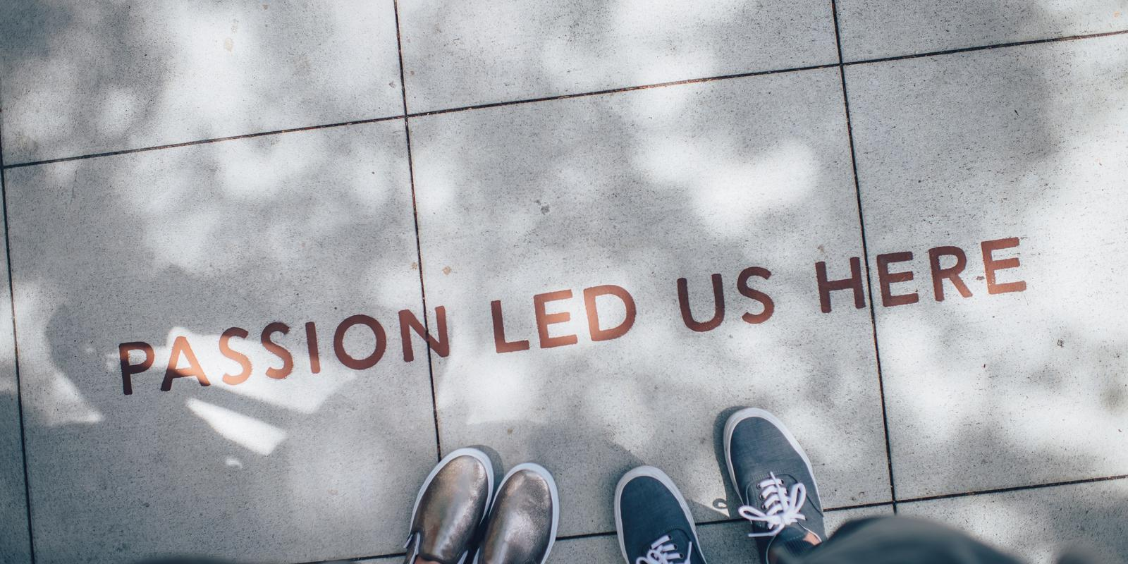 Two pairs of shoes on sidewalk that says passion led us here