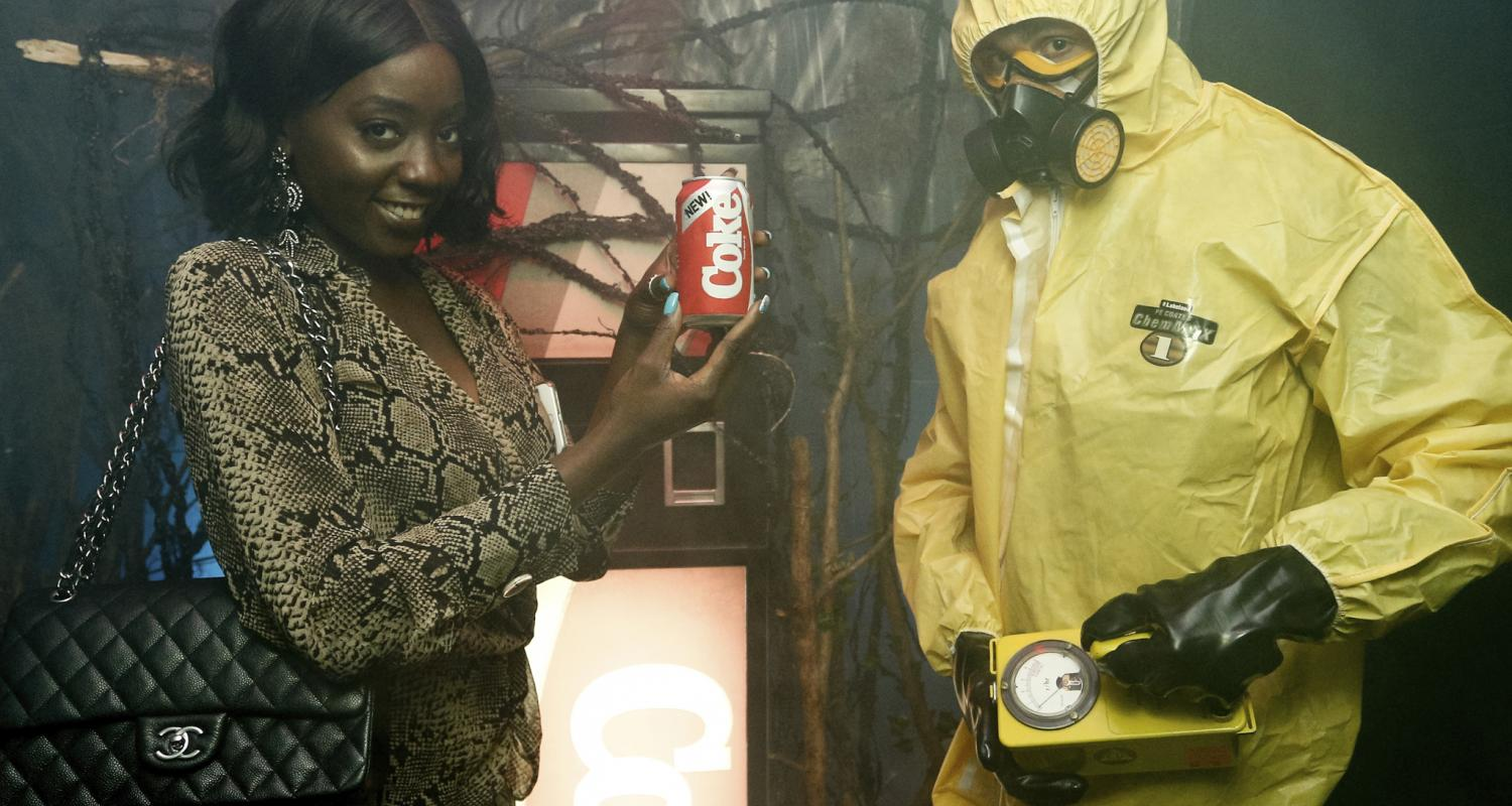 Woman in Cheetah Outfit and Man in Oxygen Mask Outfit Next to Rusty Coca-Cola Machine Image