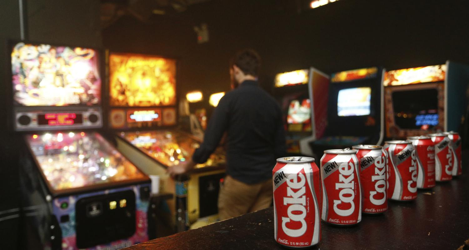 Bottles of Coke on Bar Table Next to Arcade Games Image
