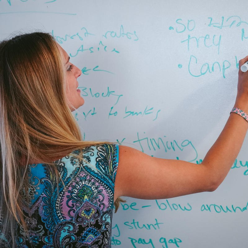 Zeno New York staffer writing on a whiteboard